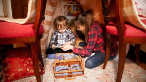 Teenage girl playing with her little toddler brother in tent at bedroom. Teenage girl playing with her toddler brother in tent at bedroom Stock Photo