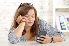Teenage girl playing with her phone Royalty Free Stock Photography