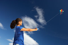 Teenage girl playing with a kite Royalty Free Stock Photo