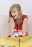 Teenage girl playing playstation. Happy blond teenage girl playing playstation at home stock photo