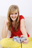Teenage girl playing playstation. Happy blond teenage girl playing playstation and winning the game stock photo