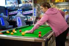 Teenage girl playing pool. Young, teenage girl in pink jacket, playing a game of pool in a leisure arcade stock photo
