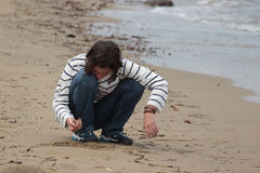 Teenage girl playing in the sand Royalty Free Stock Images