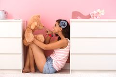 Teenage girl playing with toy bear Royalty Free Stock Image