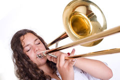 Teenage girl playing the trombone Royalty Free Stock Images
