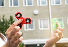Teenage girl playing with two fidget spinner. S at recess or break in school yard Stock Images
