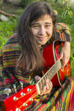Teenage girl plays guitar while sitting outdoors. Royalty Free Stock Photography