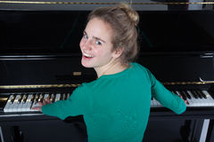 Teenage girl plays piano in green shirt stock photos