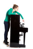 Teenage girl plays piano in green shirt Royalty Free Stock Images