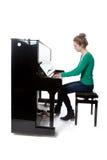 Teenage girl plays piano in green shirt stock photography