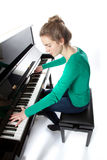 Teenage girl plays piano in green shirt Stock Images