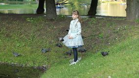 A teenage girl plays on the shore of the lake - feeds the birds, rejoices and rests. Summer park with beautiful lakes, the child walks on the shore of the pond stock footage