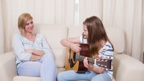 Teenage girl plays a song on the guitar to her mother stock footage