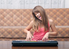 Teenage girl plays on synthesizer Stock Image