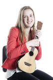 Teenage girl plays ukelele in studio against white background Stock Images