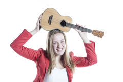Teenage girl plays ukelele in studio against white background Royalty Free Stock Images