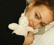 Teenage girl with plush toy rabbit. Smiling teenage girl in black pullover lying on a pillow, holding tight a pink plush toy rabbit in her arm Royalty Free Stock Photography