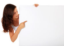Teenage girl pointing at blank white sign Stock Photo