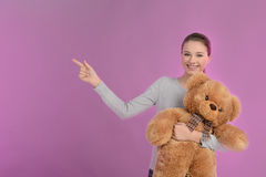 Teenage girl pointing. Happy teenage girl holding a teddy bear a Stock Image