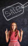 Teenage girl pointing up with forefingers at big sale sign drawn stock images