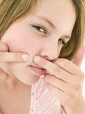 Teenage girl popping zit on face Royalty Free Stock Image