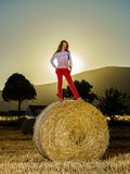 Teenage girl posing at the evening on haystack, sunset colors Royalty Free Stock Image
