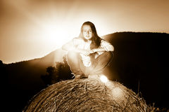 Teenage girl posing at the evening on haystack, sunset colors Stock Photo