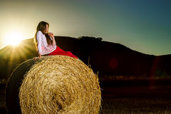 Teenage girl posing at the evening on haystack, sunset colors Stock Image