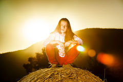 Teenage girl posing at the evening on haystack, sunset colors Stock Photography