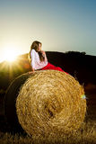 Teenage girl posing at the evening on haystack, sunset colors Stock Images