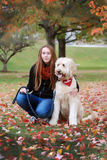 A teenage girl posing with her dog posing in leaves at Indiana University. Royalty Free Stock Photos