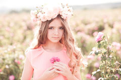 Teenage girl posing in rose garden royalty free stock photography