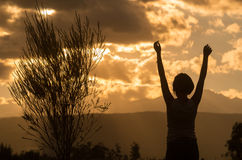 Teenage girl posing with sunset behind clouds in Royalty Free Stock Images