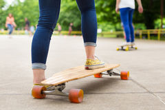 Teenage girl practicing riding long board. Royalty Free Stock Image