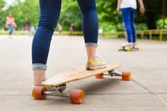 Teenage girl practicing riding long board. Royalty Free Stock Image