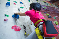 Teenage girl practicing rock climbing. In fitness studio royalty free stock photography