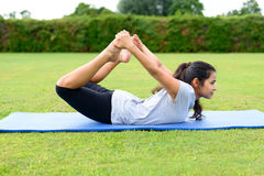 Teenage girl practising yoga outdoors. Portrait of teenage girl practising yoga on mat outdoors, Bow Position Royalty Free Stock Photography