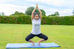 Teenage girl practising yoga outdoors. Portrait of teenage girl practising yoga on mat outdoors, Dance and Mountain Stock Images
