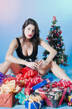 Teenage girl with presents. Teenage girl sat with pile of presents and Christmas tree, blue background Stock Photo