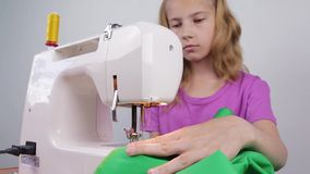 A teenage girl processes the edge of the fabric stock footage