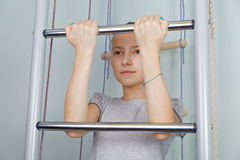A teenage girl pulls up. On a horizontal bar Stock Photo