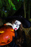 Teenage girl with pumpkin in Halloween forest Stock Images