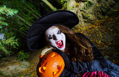 Teenage girl with pumpkin in Halloween forest Royalty Free Stock Photo