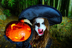 Teenage girl with pumpkin in Halloween forest Royalty Free Stock Image