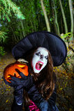 Teenage girl with pumpkin in Halloween forest Stock Photo
