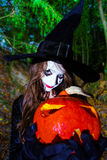 Teenage girl with pumpkin in Halloween forest Stock Photos
