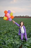 Teenage girl in purple with colorful balloons Royalty Free Stock Photos