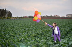 Teenage girl in purple with colorful balloons Royalty Free Stock Photography