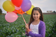 Teenage girl in purple with colorful balloons Stock Photo