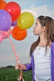 Teenage girl in purple with colorful balloons Royalty Free Stock Images